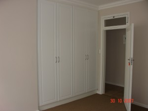 Two white melamine built in cupboards